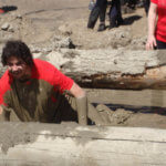 Photo Gallery: Man Crawling Underneath Log During Our Mudd, Sweat, and Tears Event