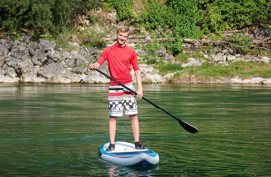a boy paddleboards in the middle of a lake during behaviour treatment recreation
