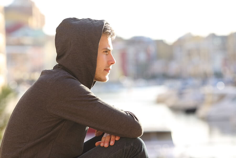 young man with hoodie on stares into the distance